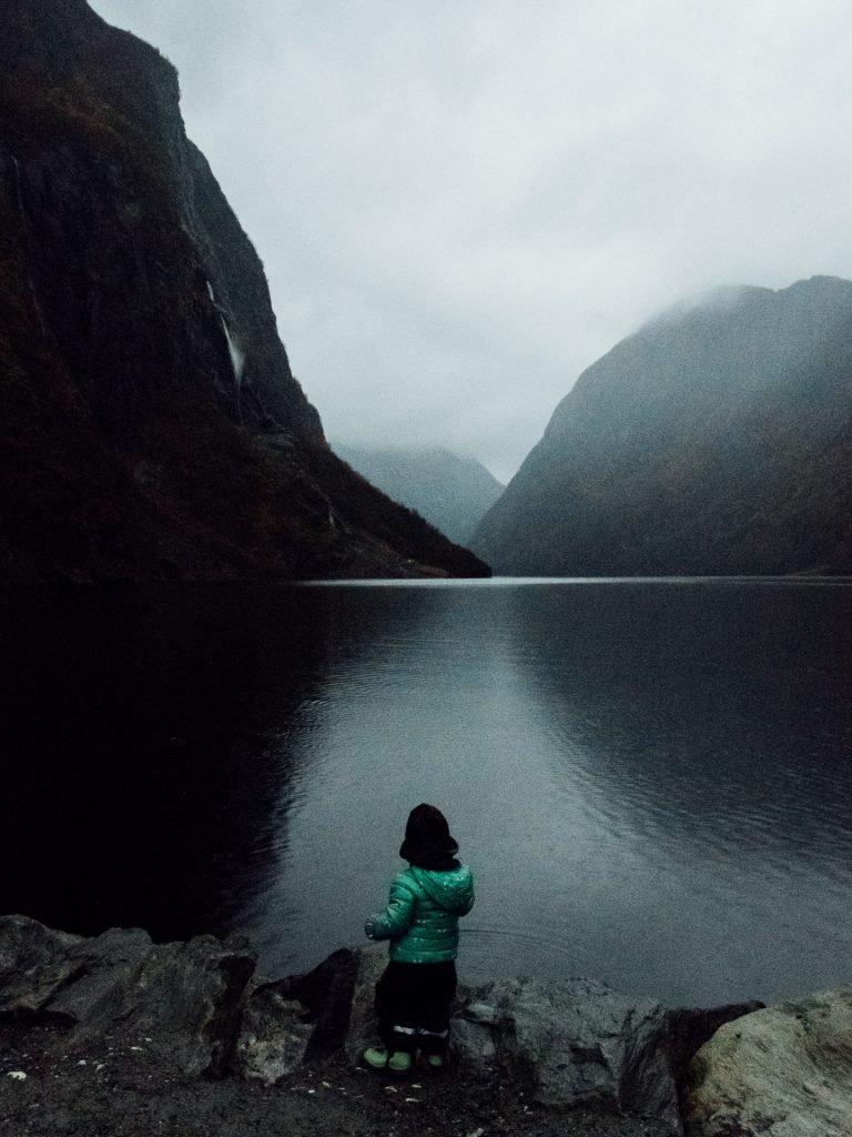 Boy standing at dusk watching Nærøyfjorden