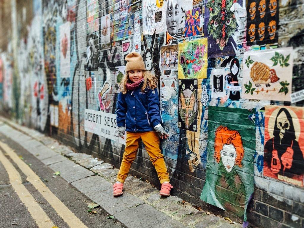 Girl in front of street art in East London
