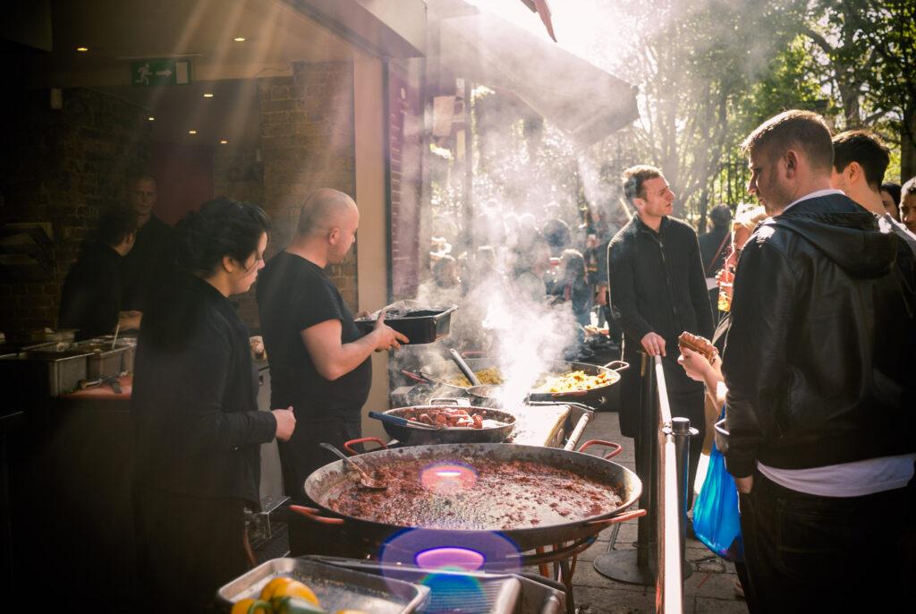 Marketgoers buying takeaway food at  Borough Market