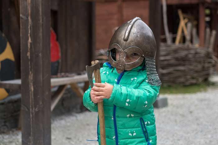 Boy in helmet using a viking battle axe