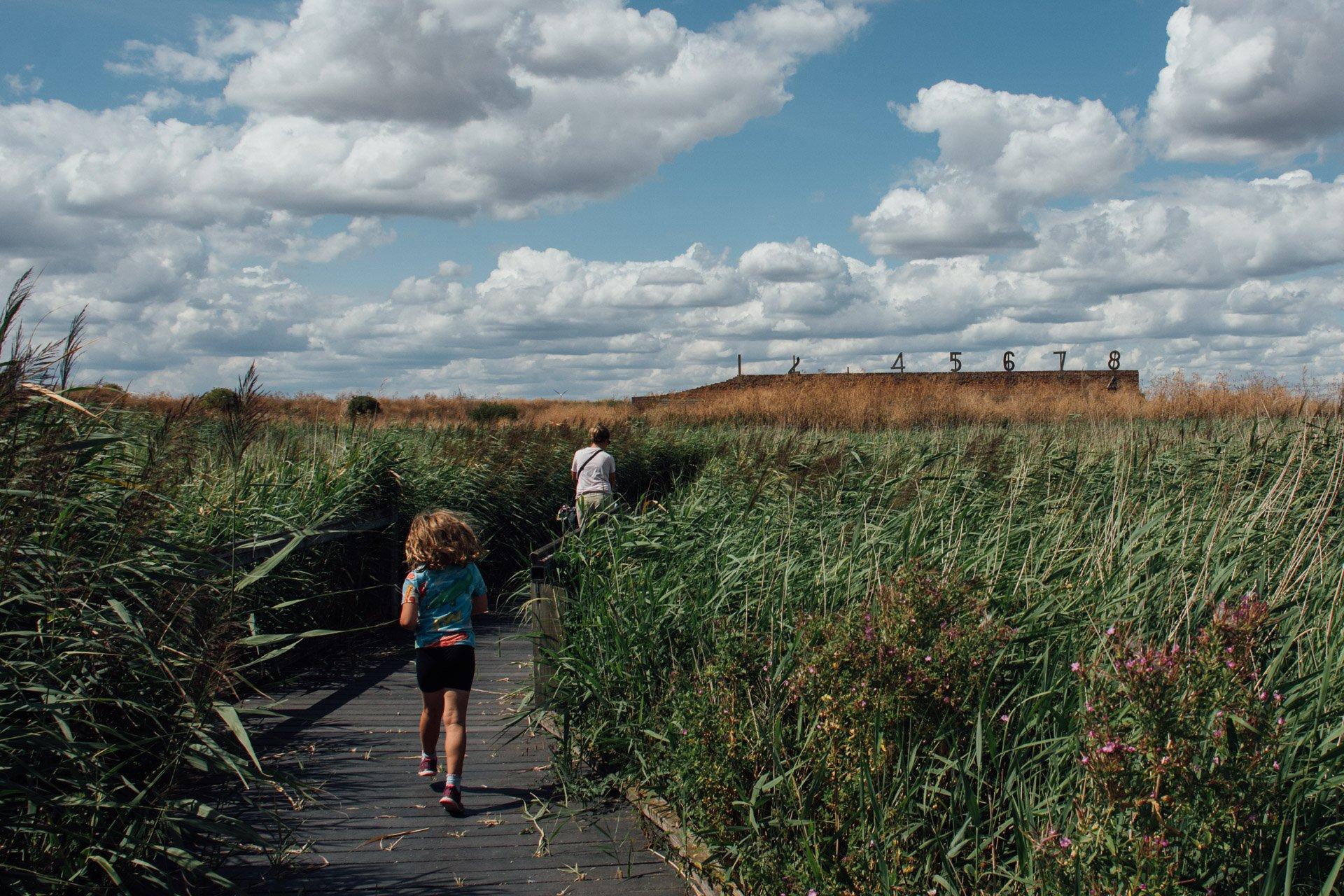 Girl running through London wetlands
